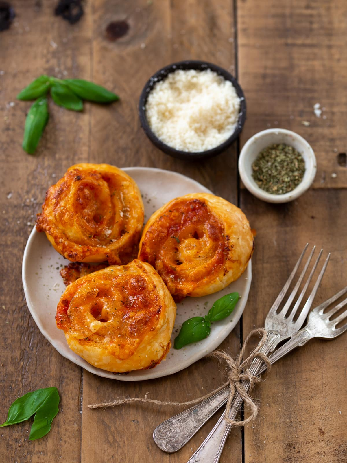 Three pizza pinwheels on a small plate.