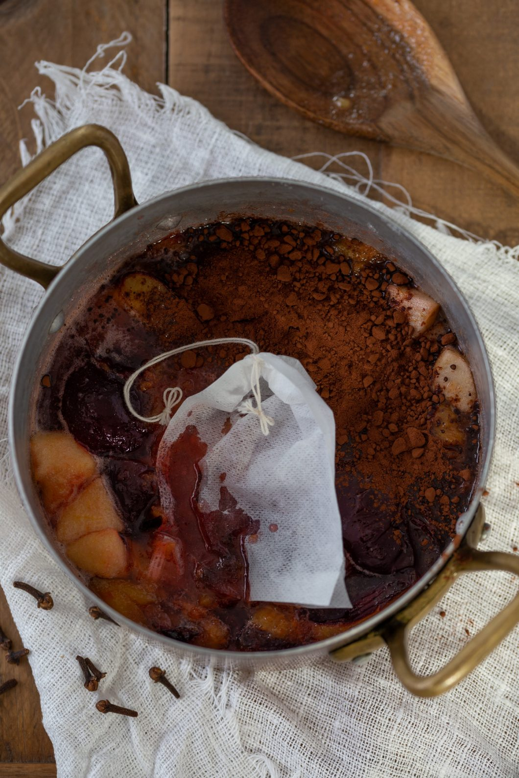 Adding cocoa and a teabag of cloves to the jam.