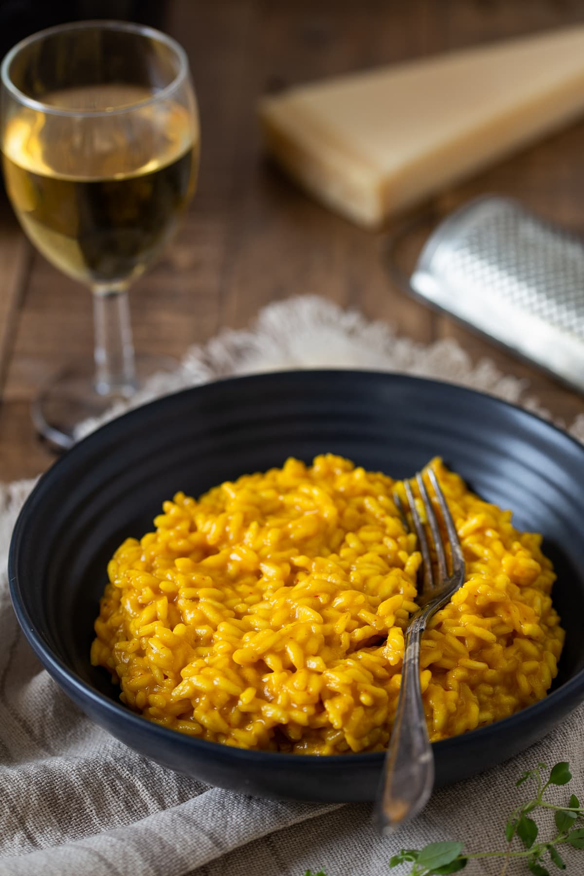 A portion of saffron risotto served with a glass of white wine.